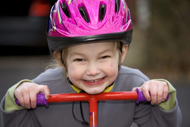 A young girl with a bicycle helmet riding a scooter