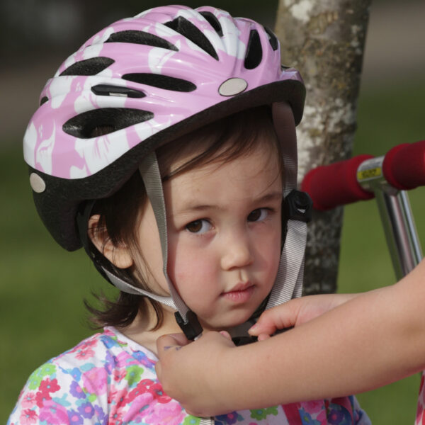 young girl having her helmet put on