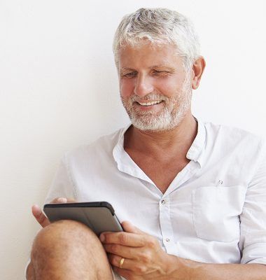 Smiling man reading ipad
